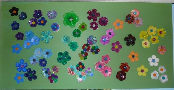 5th Grade: Flower collage on wooden board. Flowers are cut from the bottom of plastic water bottles and colored with permanent marker.