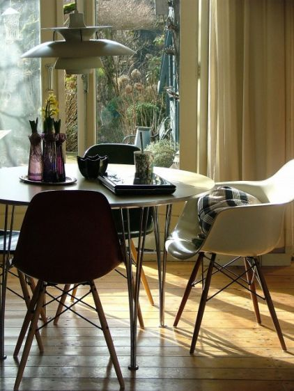 """Eames 1950s DSW (Dining Height Side Chair Wood) fiberglass armchairs and side chairs — with solid wood legs and chrome struts — encircle this mod kitchen table. These chairs were originally manufactured in organic colors such as Straw and Seafoam; turn them over and you'll likely see """"Herman Miller"""" or """"Zenith"""" (albeit rare) stamped onto the seats"""