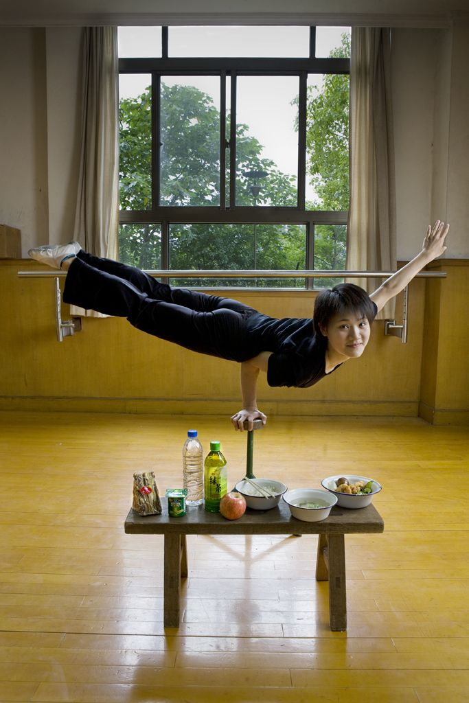 People Around the World Pose With Everything They Eat in a Day | Cao Xiaoli, a professional acrobat, balances on one hand with her day's worth of food at Shanghai Circus World in Shanghai, China. The caloric value of her day's worth of food on a typical day in June was 1700 kcals. Peter Menzel | WIRED.com