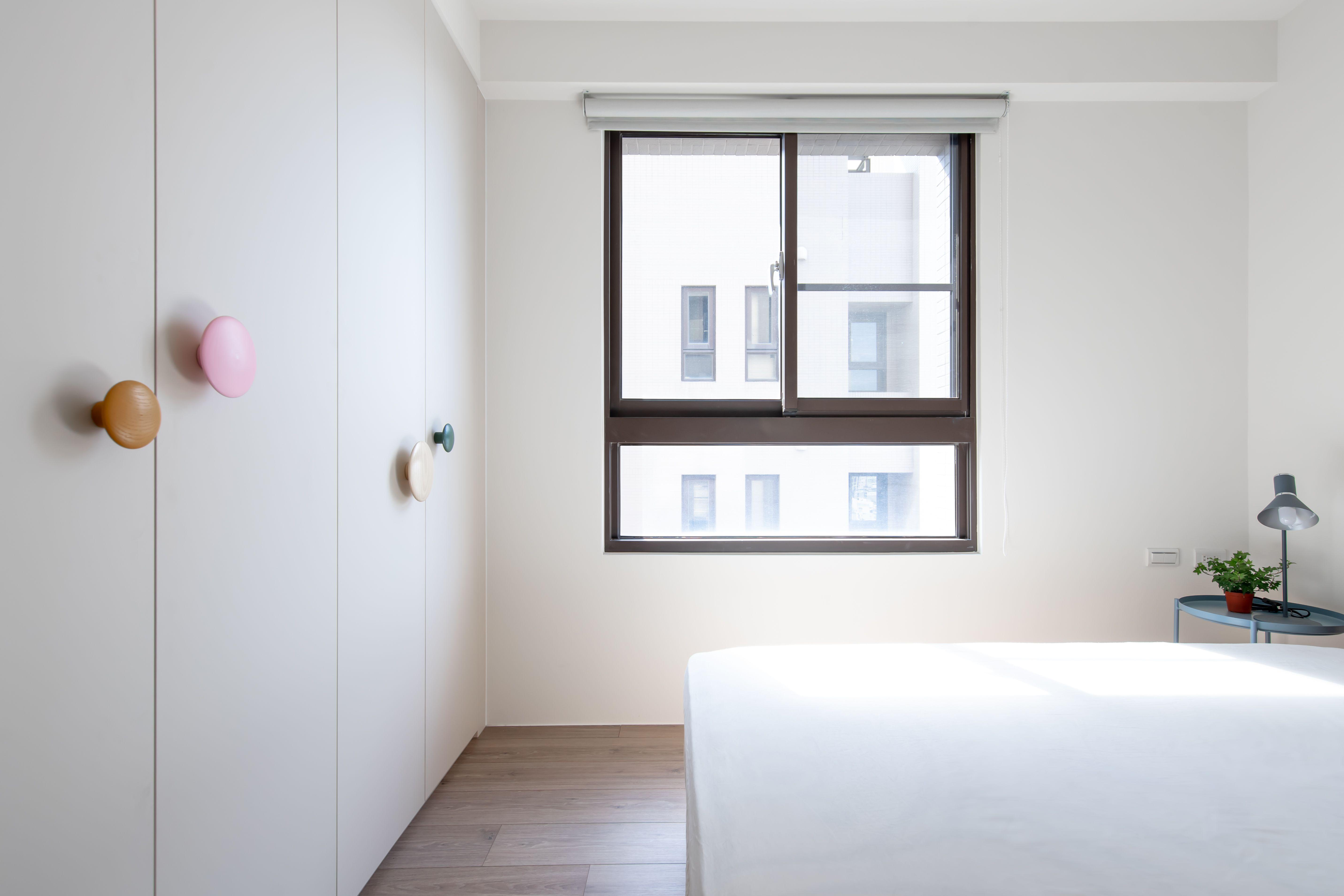 客房則是潔淨的白色極簡風格 將原木跳色掛勾做為妝點櫃體的把手 搭配
