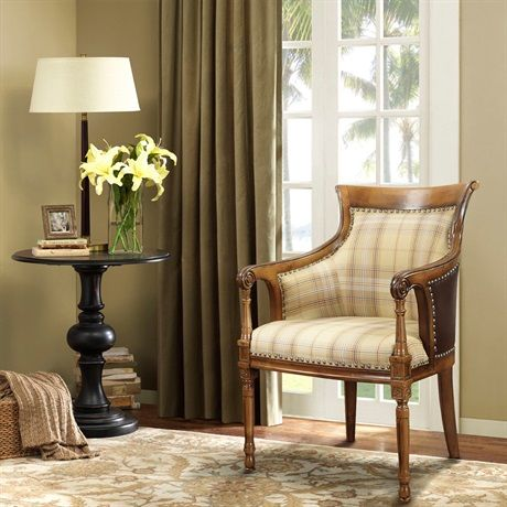A classic carved accent wood chair featuring hand carved details, outside bonded leather and soft, plaid upholstered seating. Features individual nailhead trim throughout.