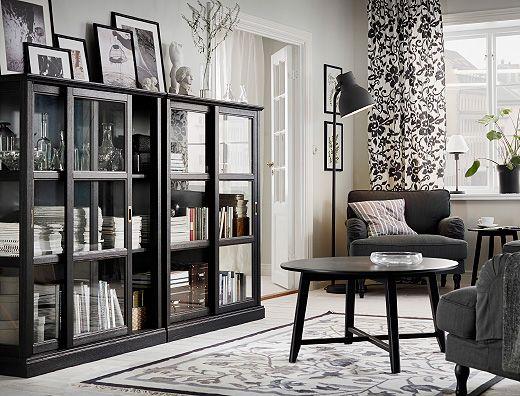 Soggiorno con poltrone grigio scuro, tavolino nero e due mobili neri con ante a vetro scorrevoli – IKEA