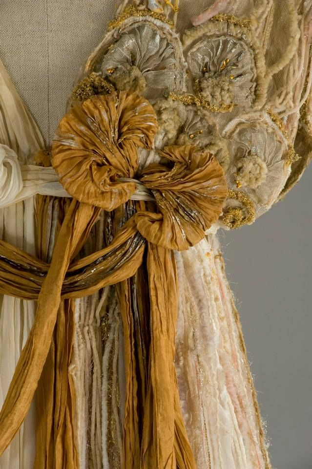 "Tunica created combining silk pleated inserts of different lengths, in shades of ivory and orange.From the left shoulder, down to Earth, a flesh-colored spark cloth, embroidered in its full length, with chenille yarns, threads and gold tulle, giving life, beautiful grounds. And orange pleated silk drapery. Time: Fantasia Costume designed by Gabriella Pescucci, made by Tailoring Tirelli in 1998. For the role of ""fairy"" in the film A Midsummer night's dream directed by Michael Hoffman. Detail"
