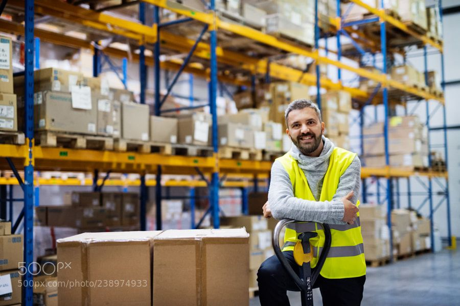 Male Warehouse Worker Standing By A Pallet Truck Warehouse