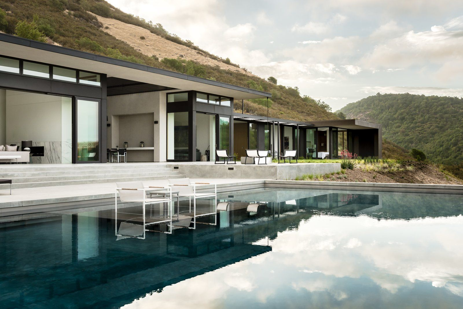Modern home with outdoor, back yard, slope, grass, large pool ...
