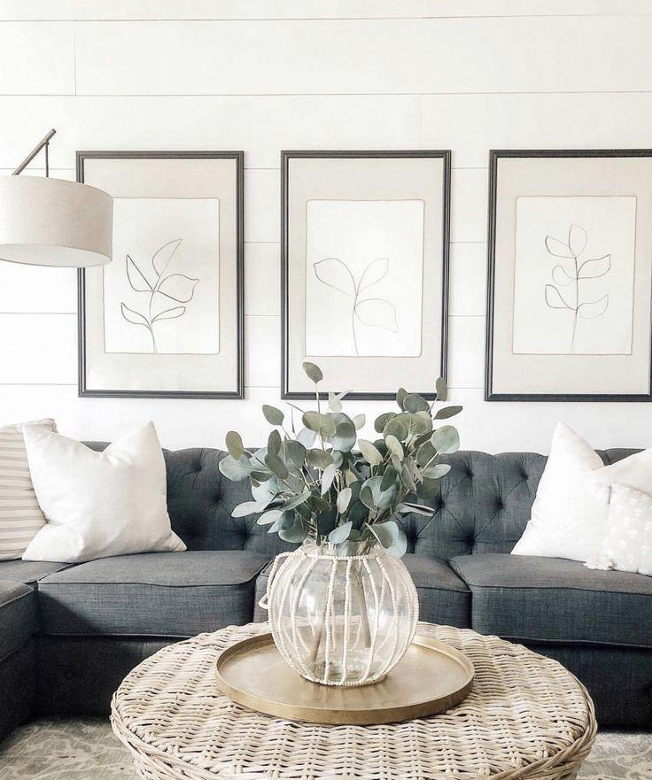 Photo of farmhouse living room with rattan coffee table decor, tufted gray sofa with farm…