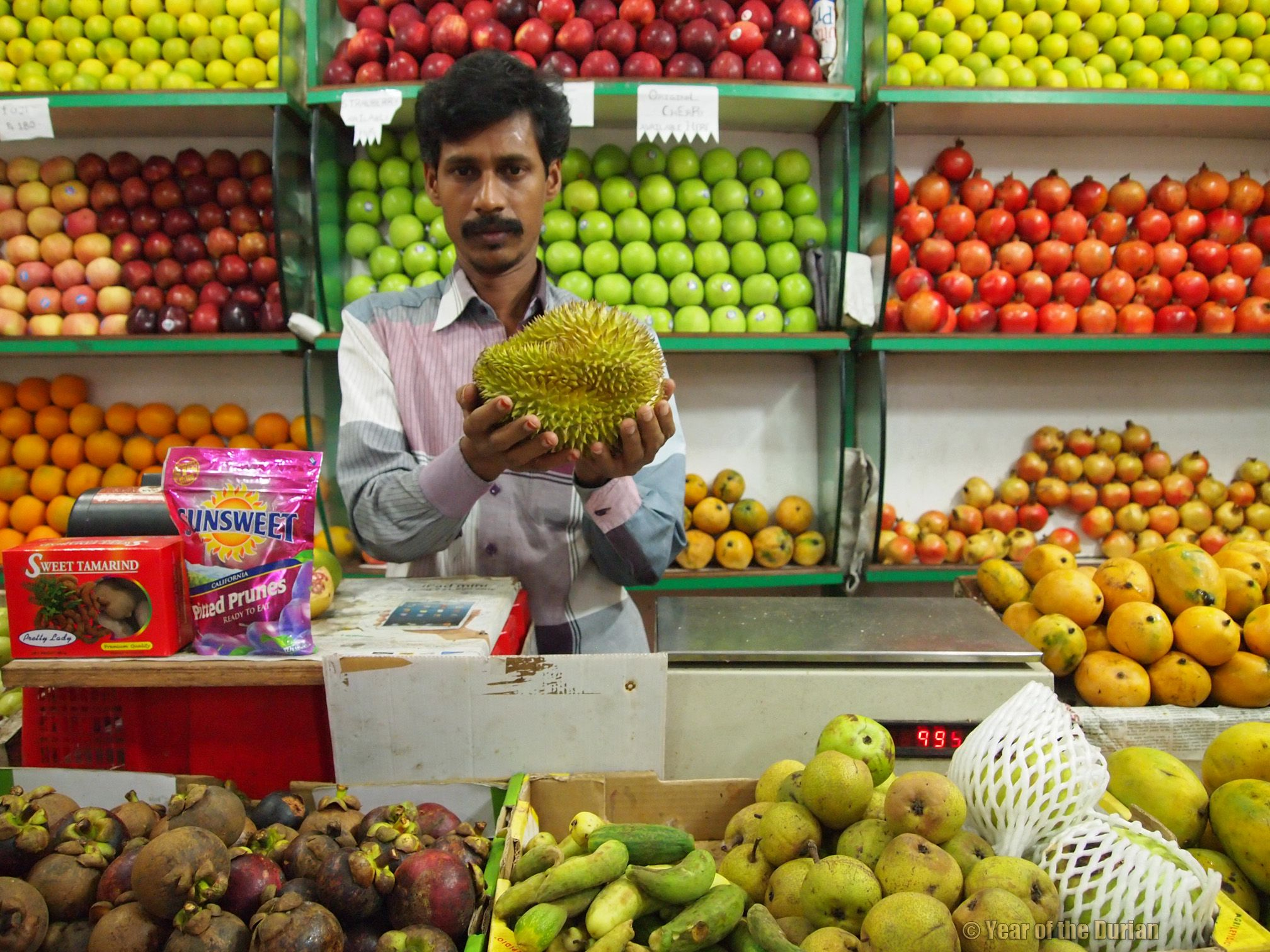 A fruit seller shows off his durian in Mettupalayam, Tamil