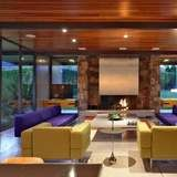 The living room fireplace in Leonardo DiCaprio's Palm Springs estate fits right in with the mid-century modern aesthetic. There's a projector screen over the hearth, in lieu of the more standard flat-screen TV.