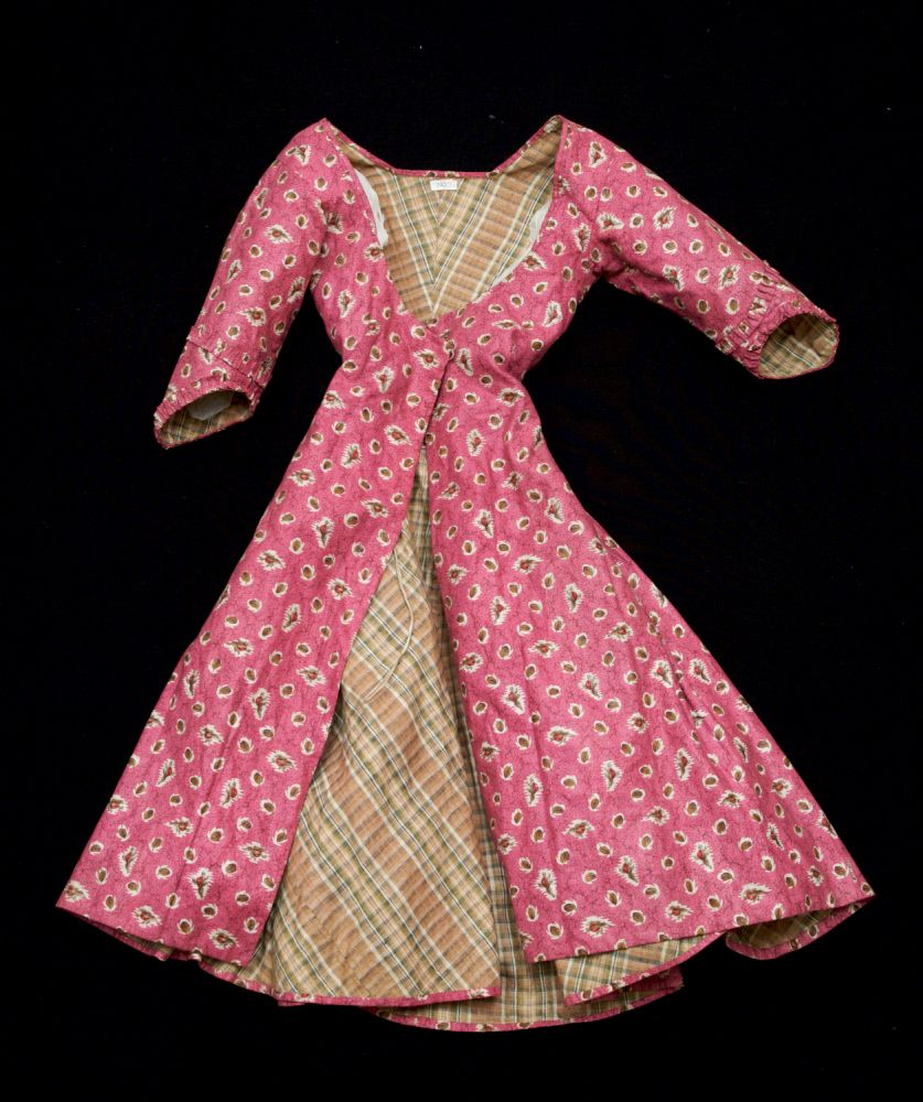 Caraco, 1780-1790. Glazed cotton, printed with red rosebuds and brown leaves on printed pink background. Lined tartan-woven cotton throughout.