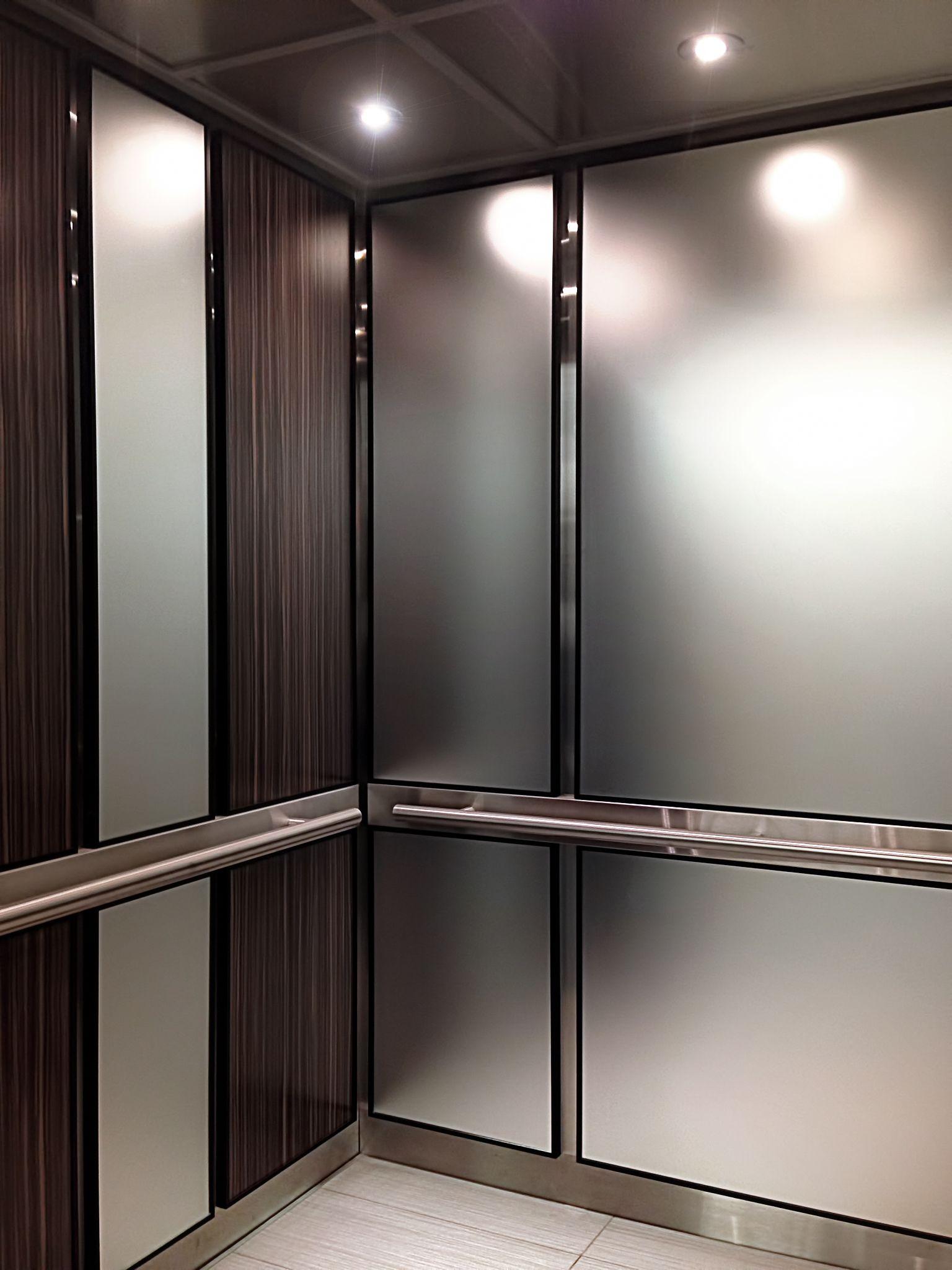 Aqua Frosted Mirror Panels Provide A Smokey Reflection Of The Wide Grain Lacquered Wood Veneer Panels Creating Elevator Interior Elevator Design Frosted Mirror