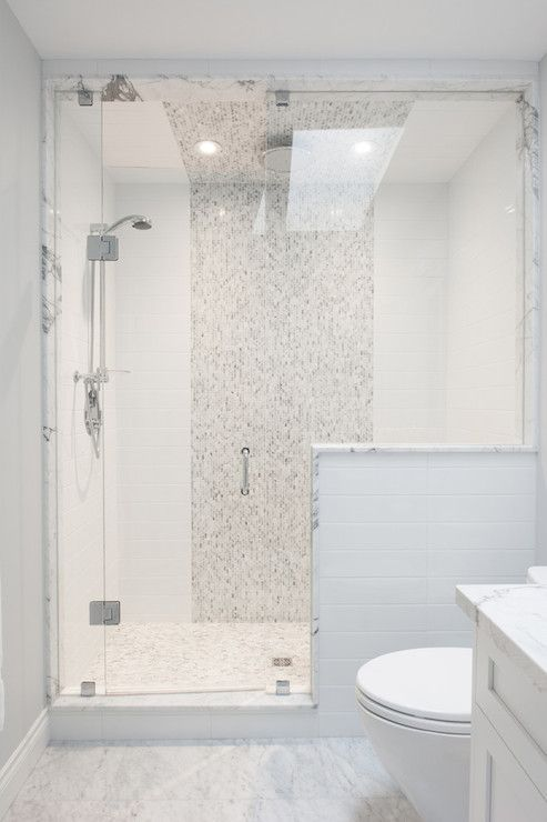 Exquisite bathroom with marble tiled floors and seamless glass front shower  framing subway tiled interior with wide marble mosaic tiled vertical stripe  ...