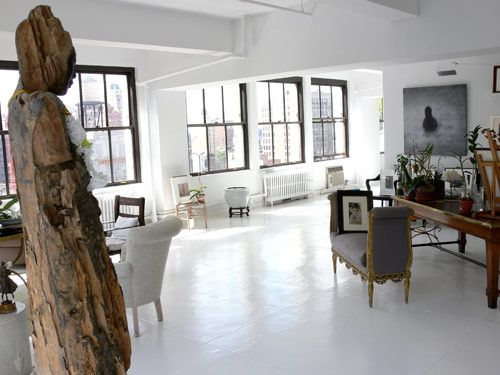 Streams Of Light Are Reflected Off The White Painted Concrete Floors And Walls In Living Room