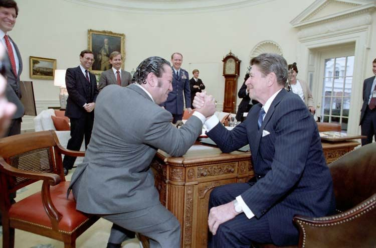 Ronald Reagan arm wrestling with Dan Lurie from Muscle Training Magazine in oval office. 2/16/84.