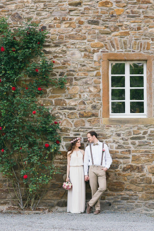 Boda rústica, recién casados de pie frente a un muro de piedra, fotografía de bodas