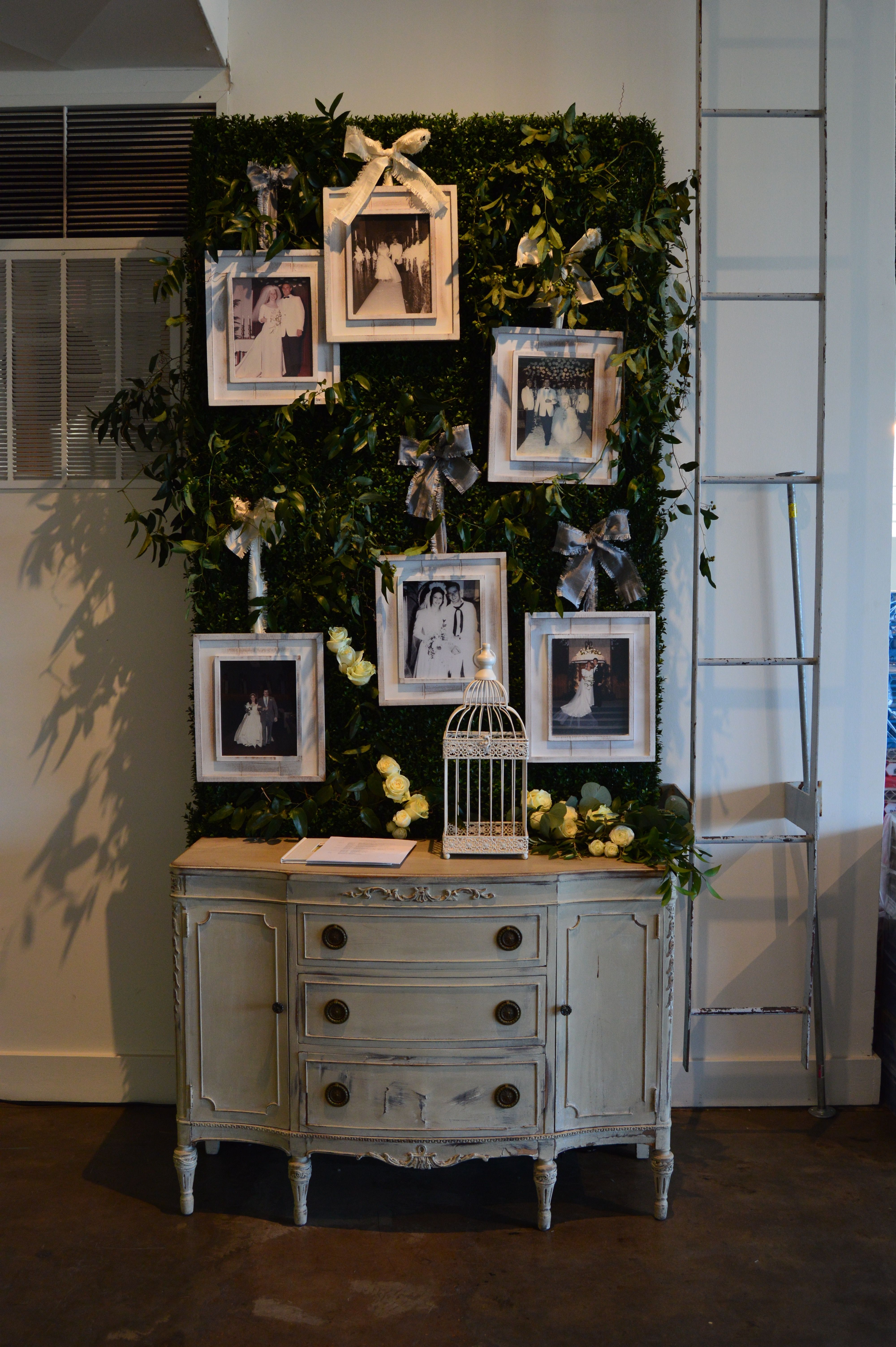 Our hedge wall accented with live greenery and personalized photos at the guest book. Make those small moments in your wedding magic!