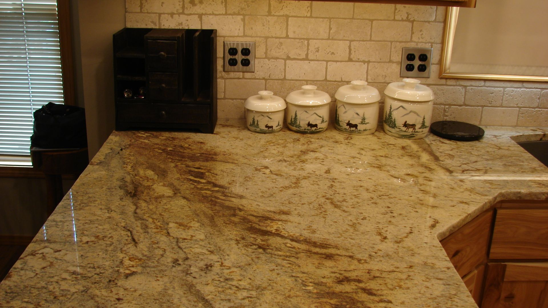 3cm typhoon bordeaux granite counter with tumbled travertine backsplash