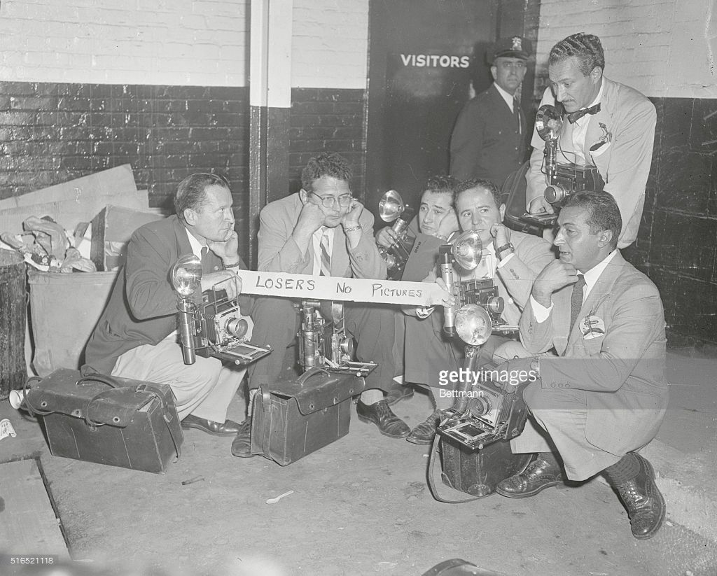 World Series. Dodgers & Yankees. Ebbets Field. Brooklyn, New York: Group of photographers, assigned to Yankees, sit forlornly outside of losers' dressing room. They were not admitted into Yankee dressing room. October 1, 1952.