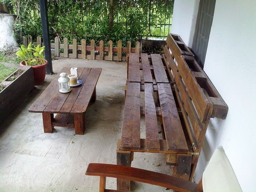 Now coming towards a more domestic and typically made sitting arrangement again made suing the shipping wood pallets. Not only the bench and the table is made with pallets, but we also see some raw wooden pallet planters and the fencing as well all around the sitting space.