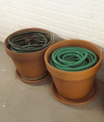Keep garden hoses contained and neatly stored in big pots that aren t being used