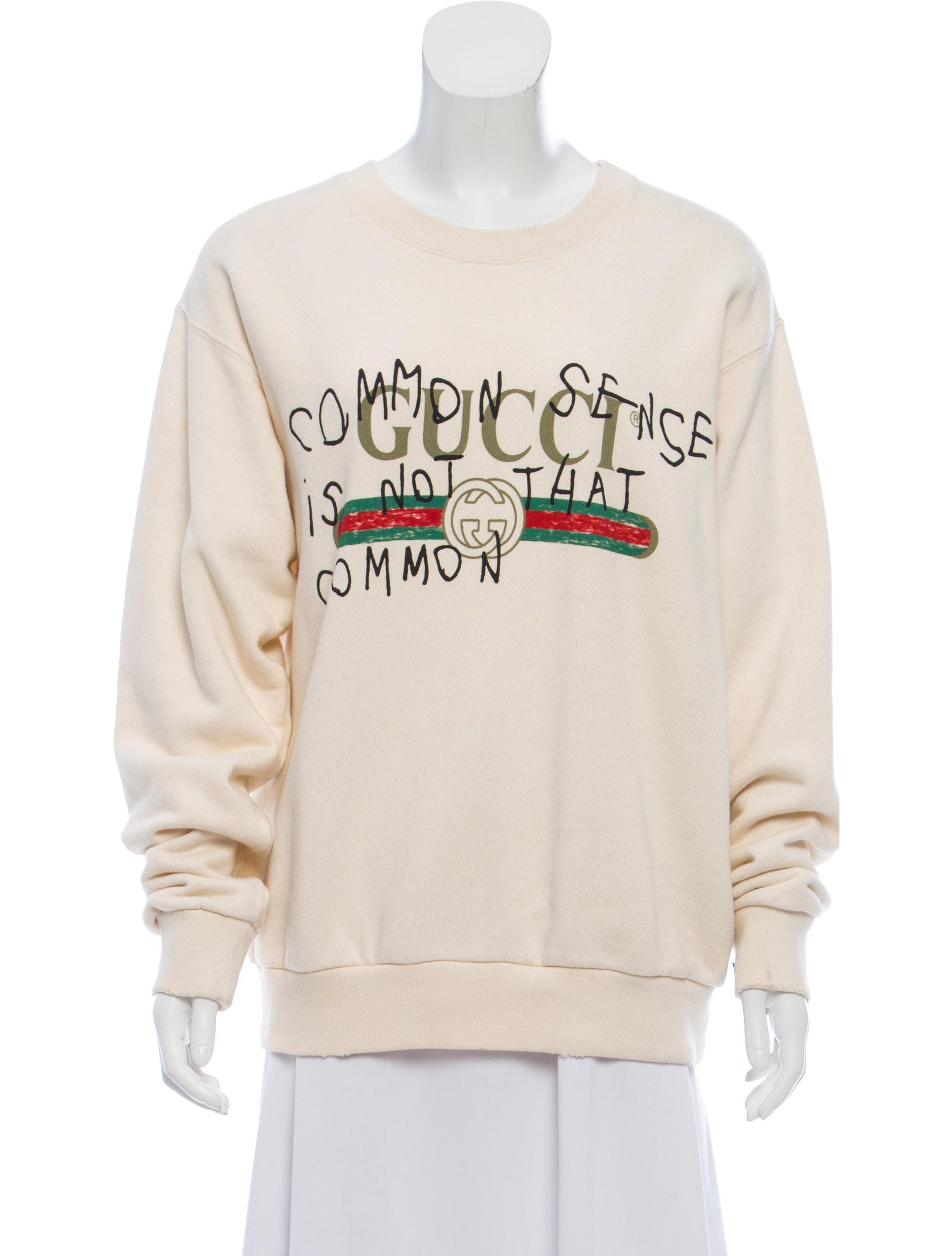 6e2559472 From the 2017 Collection. Creme Gucci Coco Capitán sweatshirt with long  sleeves, crew neck, rib knit trim, logo graphic print and lettering at  front.