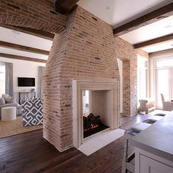 Transitional kitchen features a brick two sided fireplace with see ...
