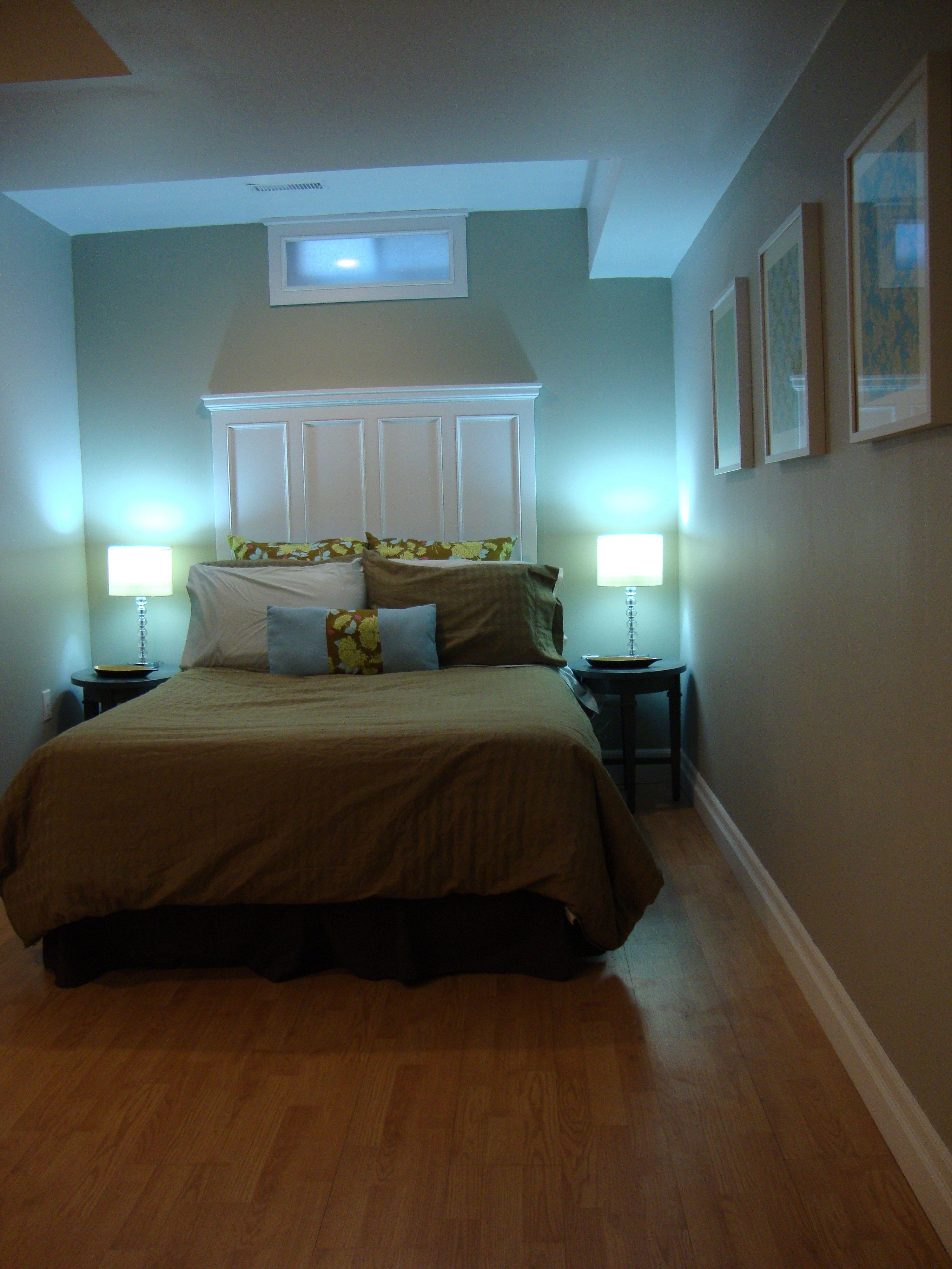 Clean simple basement guest bedroom. Headboard. Blue