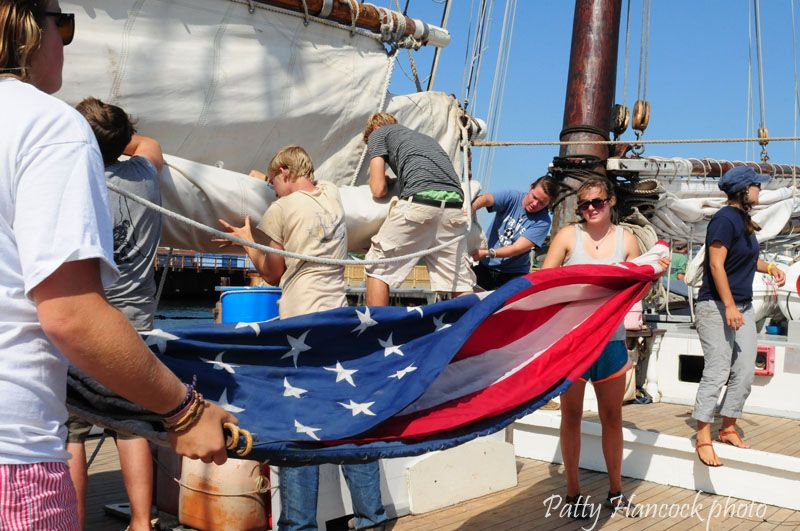 "Folding the flag on the schooner ""Harvey Gamage""."