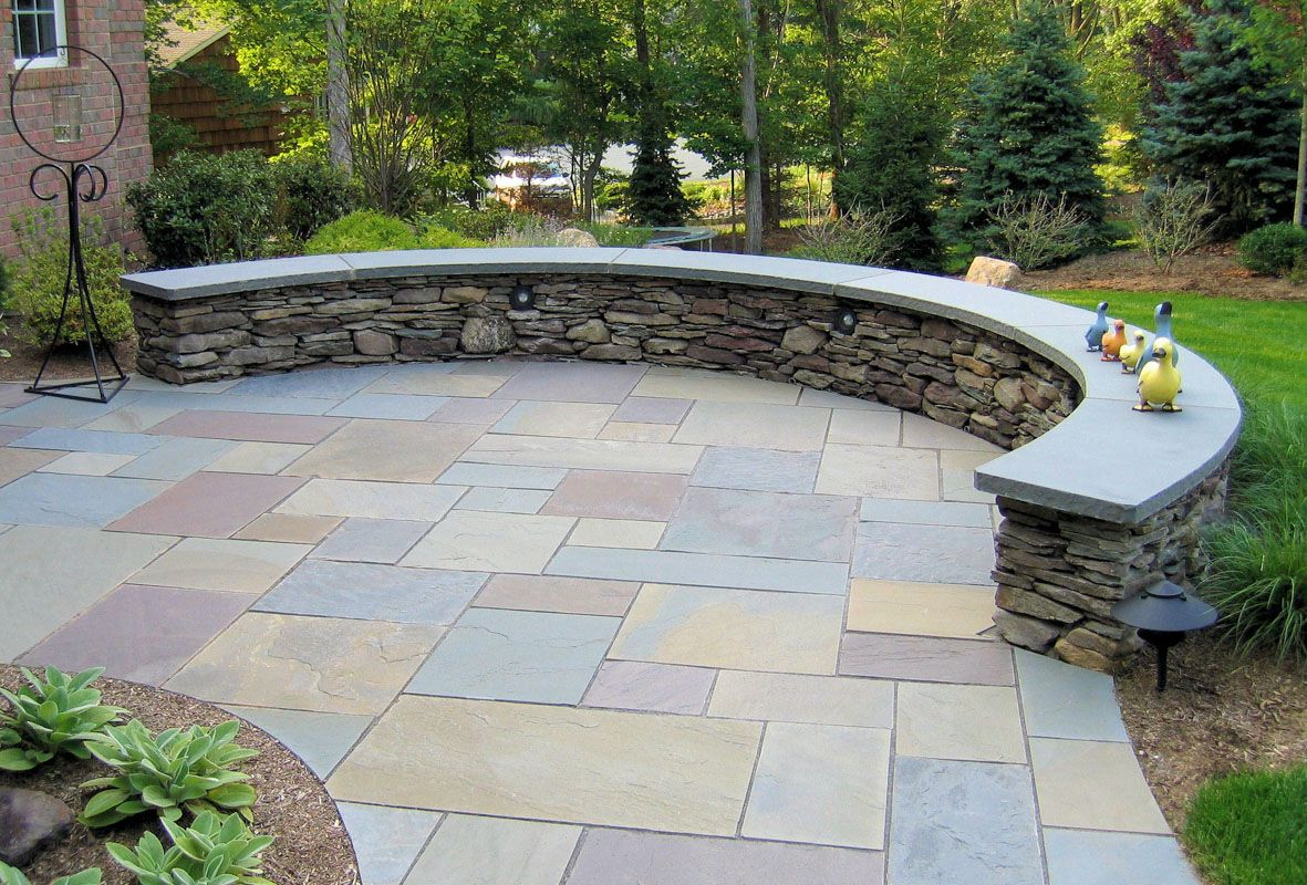 Curved fieldstone ledge sitting wall with bluestone cap for Patio and landscaping ideas