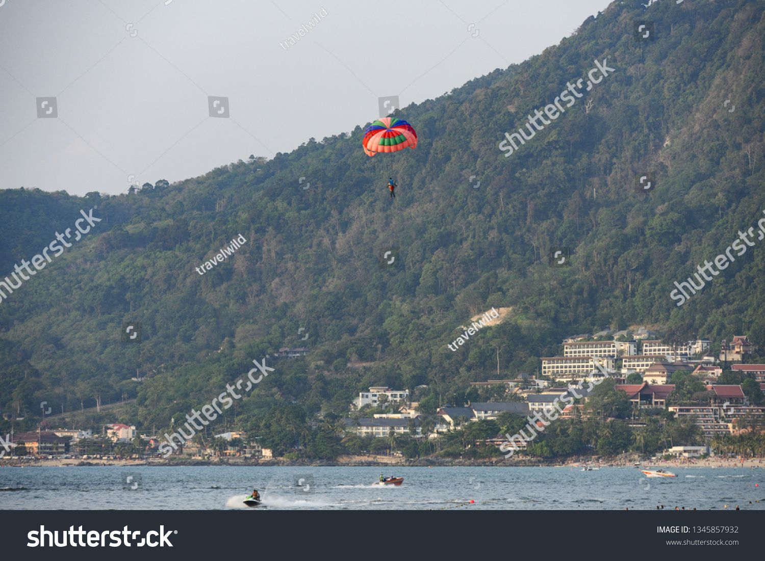 PATONG BEACH  PHUKET  THAILAND  FEBRUARY 24 2019 Some tourists swim while some other people do parasailing in the background Phuket Thailand Parasailing is a recreational...