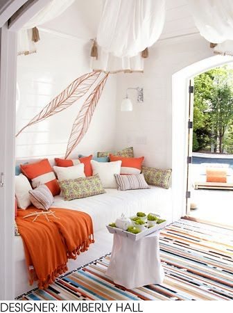 sherbet-colored back porch. So cozy!!!  love the wall art
