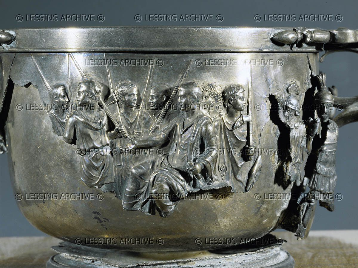 So-called cup of Emperor Augustus( detail): Augustus, on a folding chair and surrounded by lictors, receives the submission of the barbarians. Behind him two officers. From the Treasure of Bosocoreale, end 1st BC. Silver.