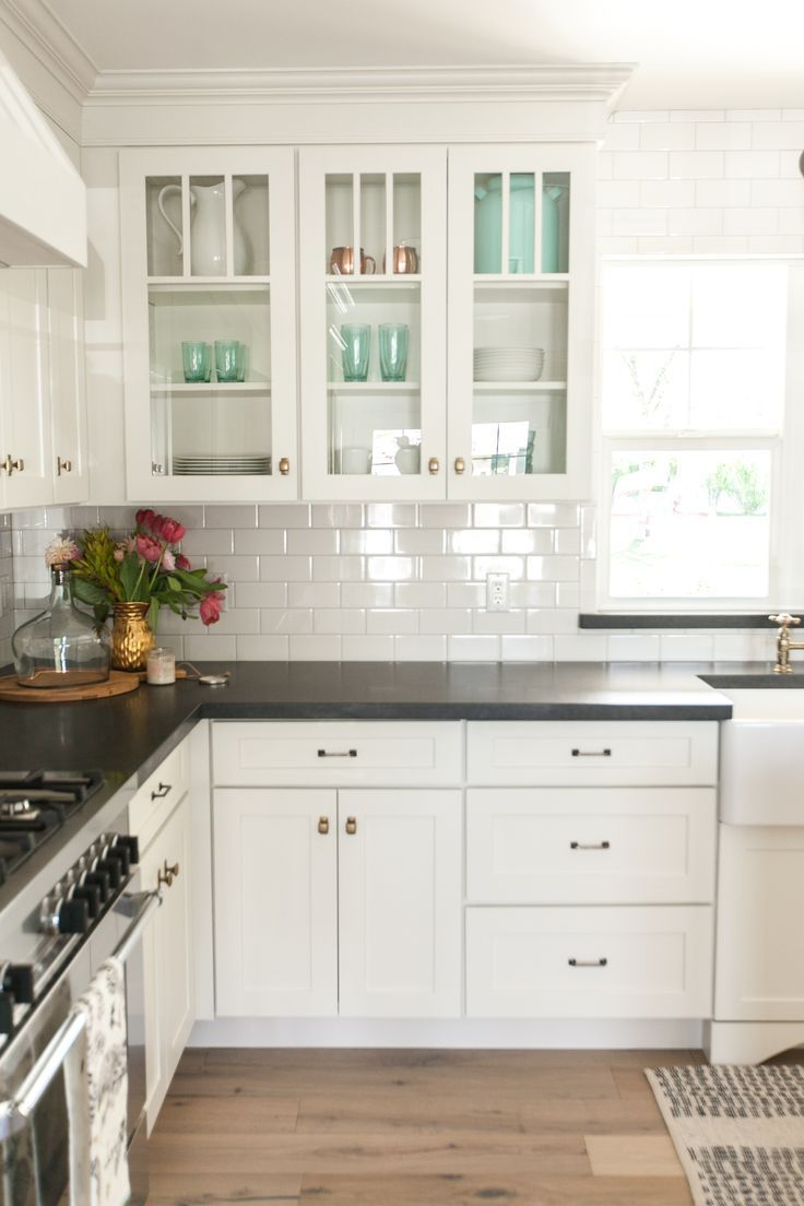 White kitchen cabinets, black countertops and white subway tile with ...