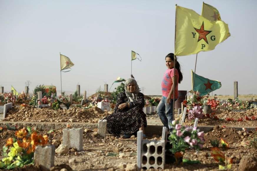 Een Syrisch-Koerdische vrouw bij het graf van een familielid die is omgekomen in de strijd met terreurbeweginging Islamitische Staat.
