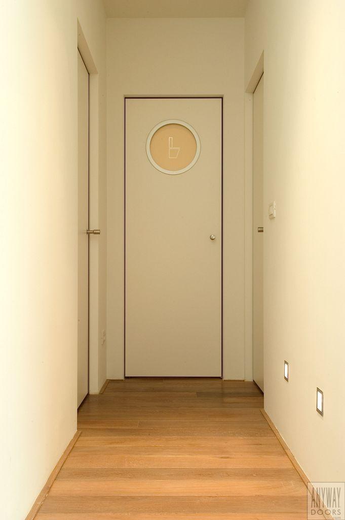 Moderne binnendeur met speelse patrijspoort voor toilet en een onzichtbare omlijsting.