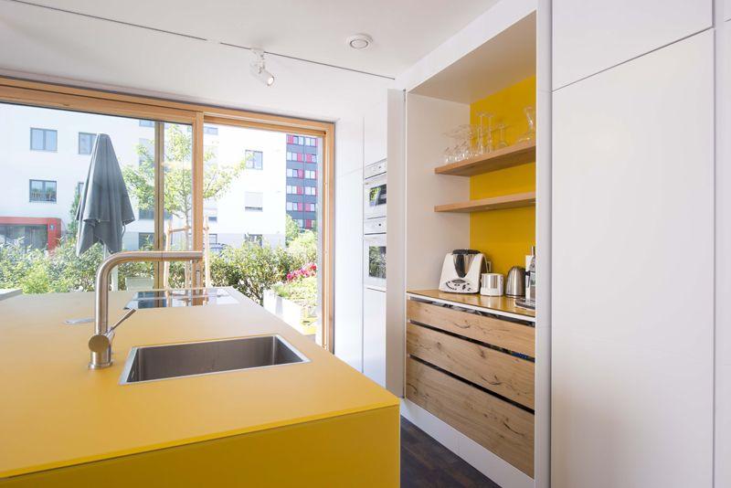 Gelbe Kücheninsel Von Lago, Arbeitsfläche Der Kochinsel Aus Glas. Hinter  Der Taschentüre Kommt Eine