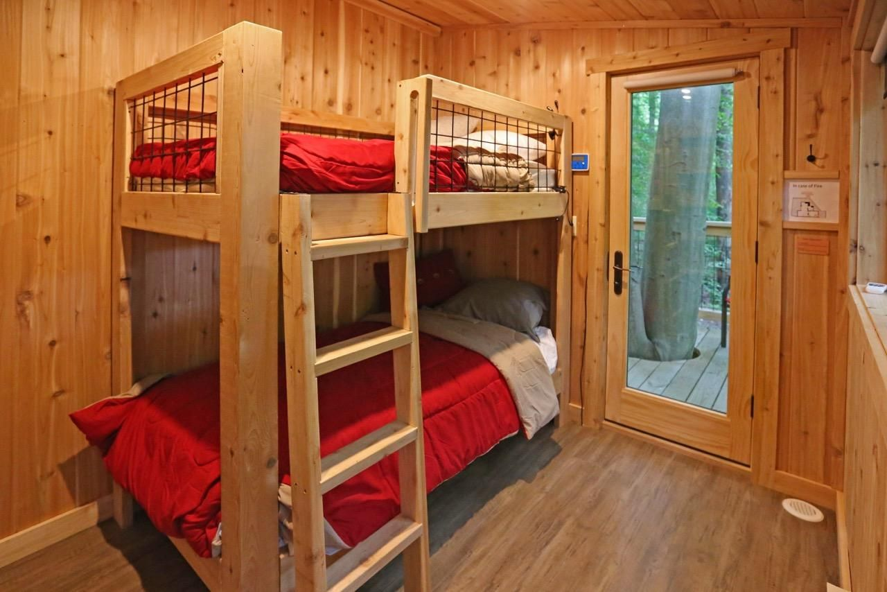 A hidden door bookcase leads to a bedroom with twin bunk