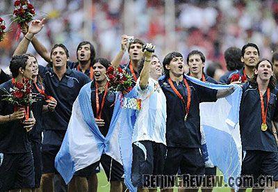 Estos son un grupo de hombres en los Juegos Olímpicos. El equipo de Argentina están celebrando. Tienen medallas olímpicas alrededor de sus cuellos y se mecen su bandera Argentina.