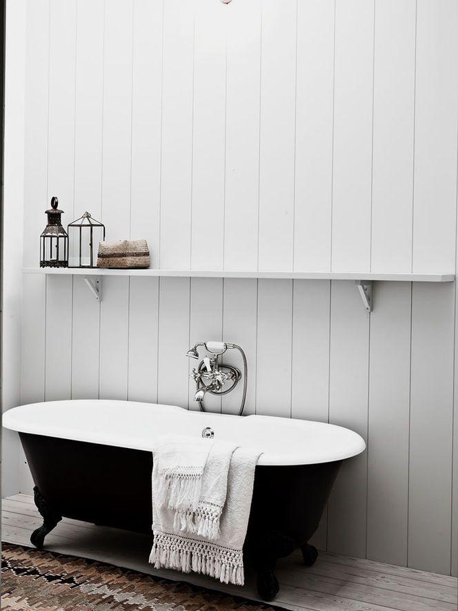 Black bath tube, white wood walls and a long shelf to put all the ...