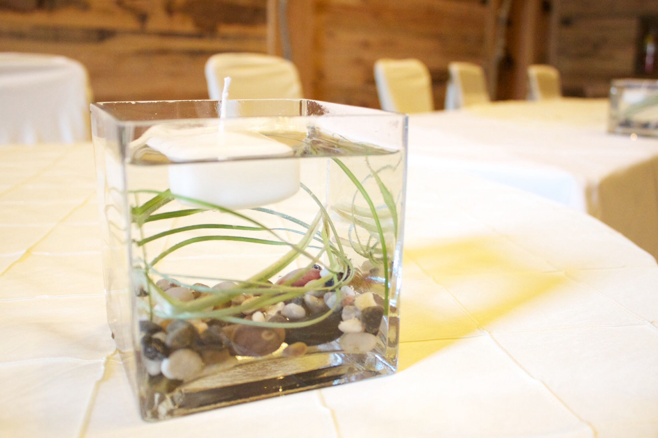 Simple stone and grass centerpiece with floating candle | Sundance ...
