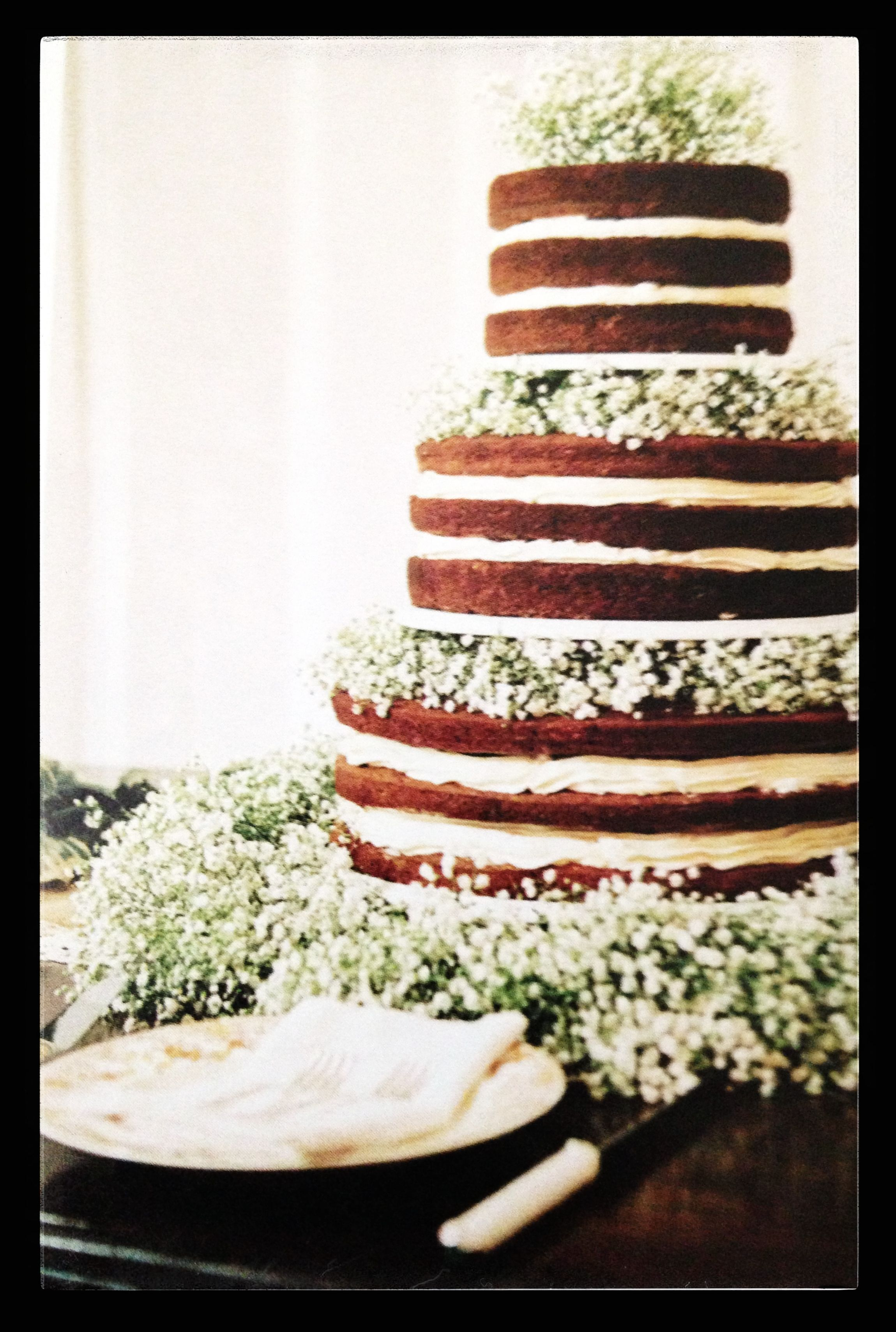 This just might happen!!! Baby's Breath accenting unfrosted wedding cake. Rustic look!