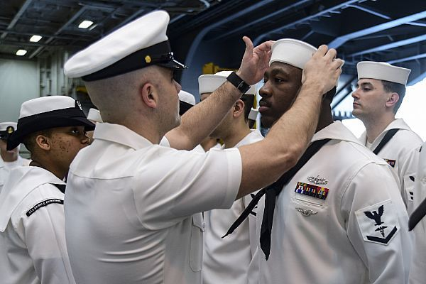 160420-N-CZ759-016 ATLANTIC OCEAN (April 20, 2016) Senior Chief Hospital Corpsman Nicholas Noviello inspects Sailors' dress white uniforms in the hangar bay of the aircraft carrier USS Dwight D. Eisenhower (CVN 69), the flagship of the Eisenhower Carrier Strike Group. Ike is underway preparing for an upcoming scheduled deployment. (U.S. Navy photo by Mass Communication Specialist 3rd Class Theodore Quintana/Released)