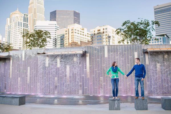 Engaged couple stand in front of Charlotte, NC fountain during e-session.
