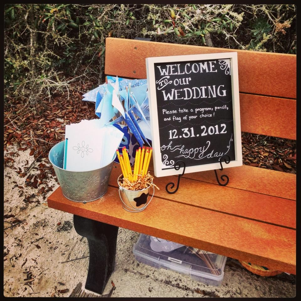 On a bench at the beach entrance:   pennant flags, programs, pencils (for word search in program) and faux-chalkboard sign