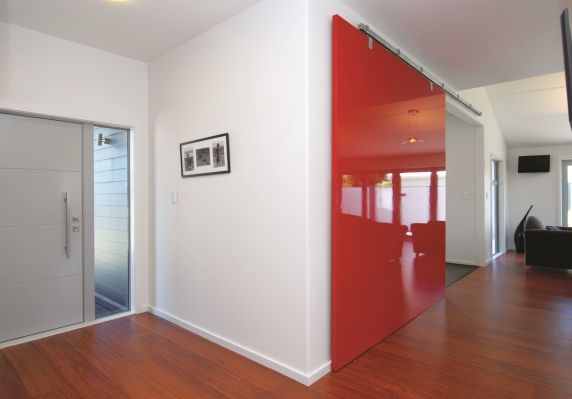 A blod red sliding door divides the family area and formal lounge, and add a pop of colour to the home.