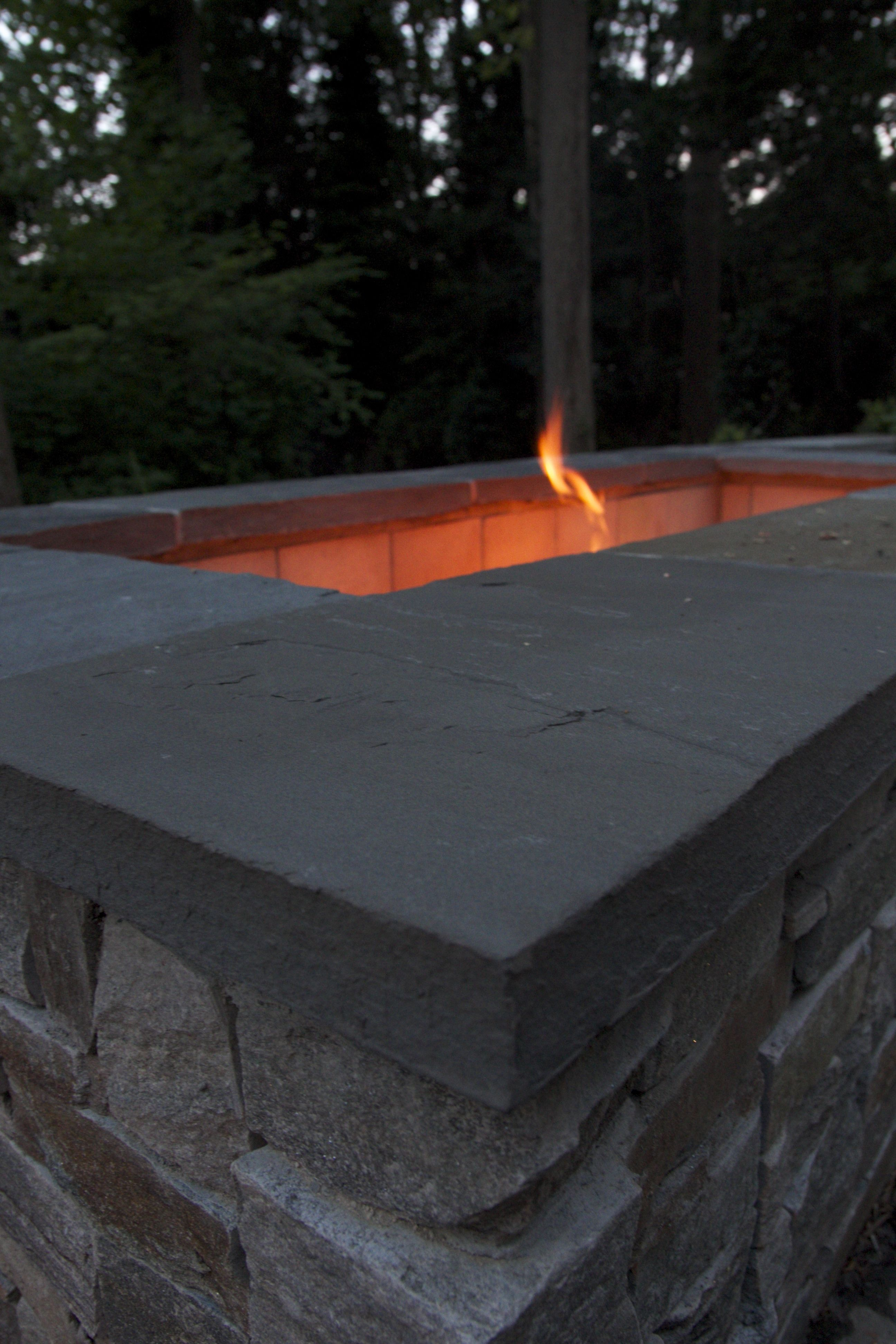 the soft glow of the stone fire pit creates a calm ambiance at night