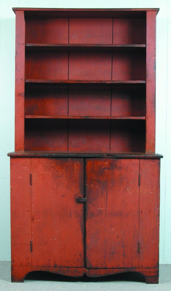 """Good Ohio or PA Early 19th Century Softwood Red Painted Stepback Cupboard, one part with three shelves over cabinet top, two door base with one fixed shelf and one upper small removable shelf, arched and shaped base with bracket feet, Ex. Ron Koehler, 79""""h. x43-½""""w. x 21-¼""""d., (minor losses to wood, front right foot restored, natural wear to original paint)."""