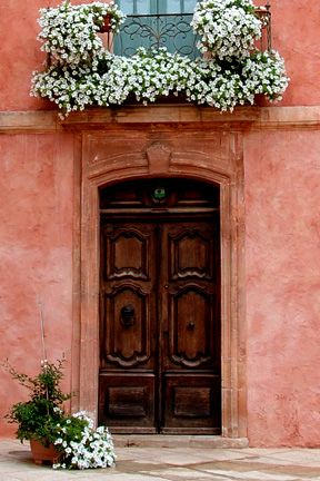 Another amazing photo, shot in Provence, France.... I Love the CORAL COLORED house paint, with the pretty white flowers throughout.