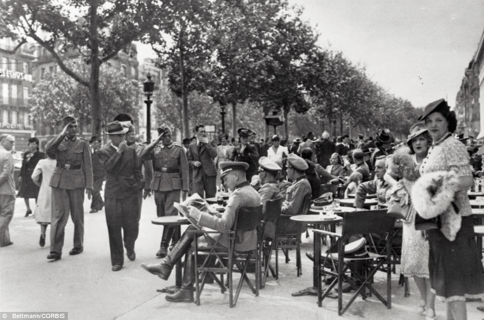 Mrs de Florian fled Paris before the outbreak of war in 1939, which saw the Nazis invade France and reach Paris on June 14. Pictured here, German officers and Parisians mingle near a sidewalk cafe on the Champs Elysees on Bastille Day in 1940