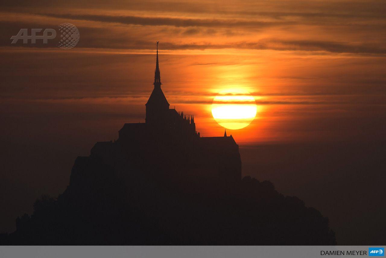 FRANCE, Mont Saint-Michel: The sun sets on the Mont Saint-Michel, a Unesco world heritage site, western France on July 15, 2013. AFP PHOTO / DAMIEN MEYER