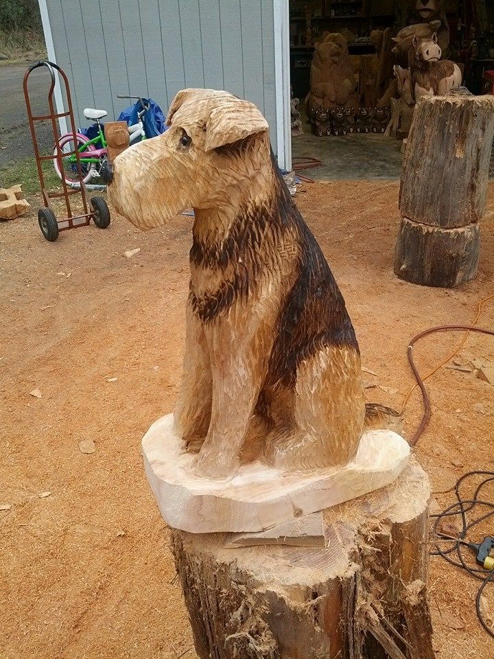 Airedale sitting dog chainsaw carving wood sculpture